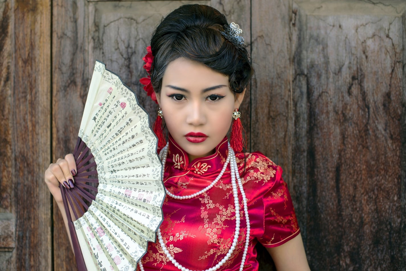 Chinese lady holding a fan, wearing red