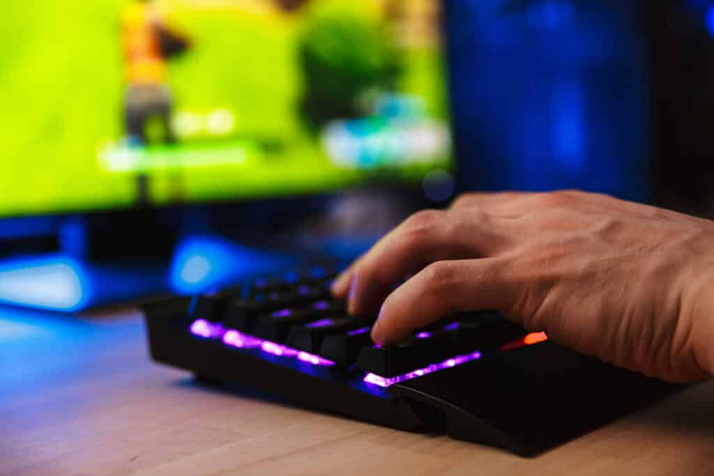 Cropped image of young gamer playing video games on computer